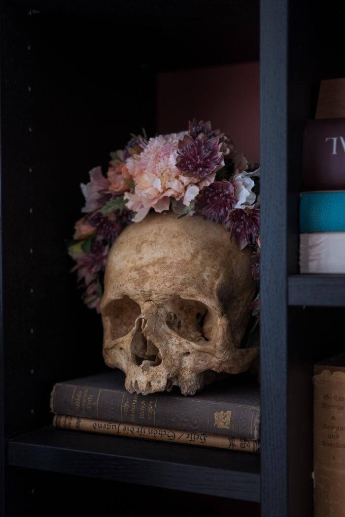 Echter Totenschädel mit Blumenschmuck.